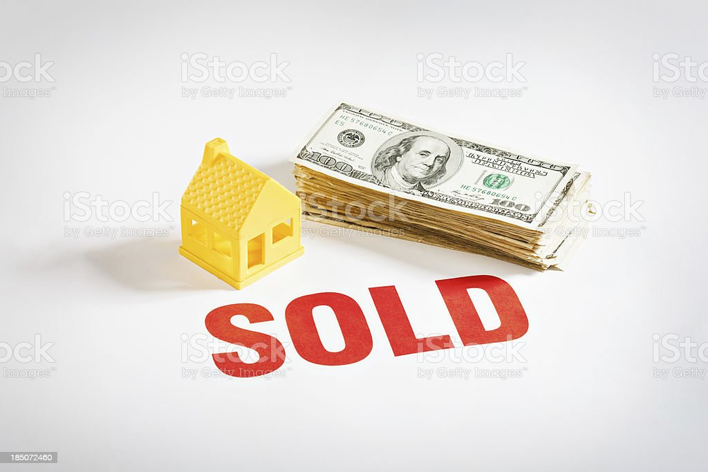 \'A yellow toy house sits next to a stack of dollars and a Sold sign....