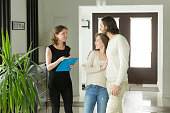 Friendly realtor or landlord talking showing modern luxury house for sale to young couple customers, real estate agent discussing rental home with renters tenants, planning property purchase concept