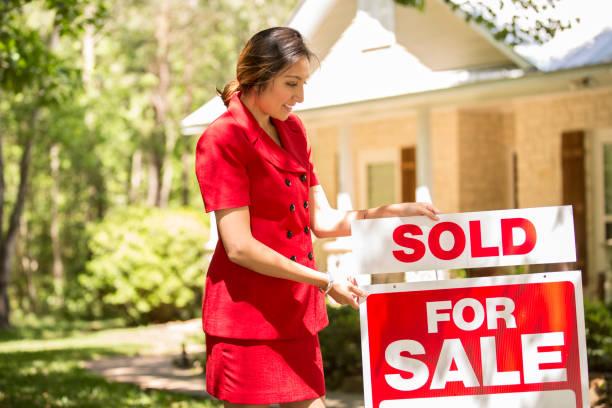 Makler vor Haus zu verkaufen mit Schild von Immobilienmakler. – Foto