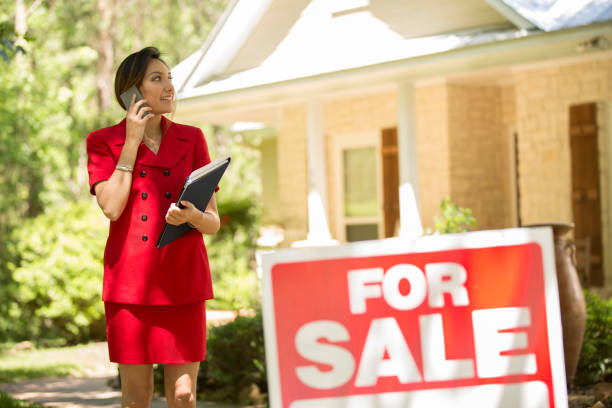 Realtor outside home for sale with real estate sign. stock photo