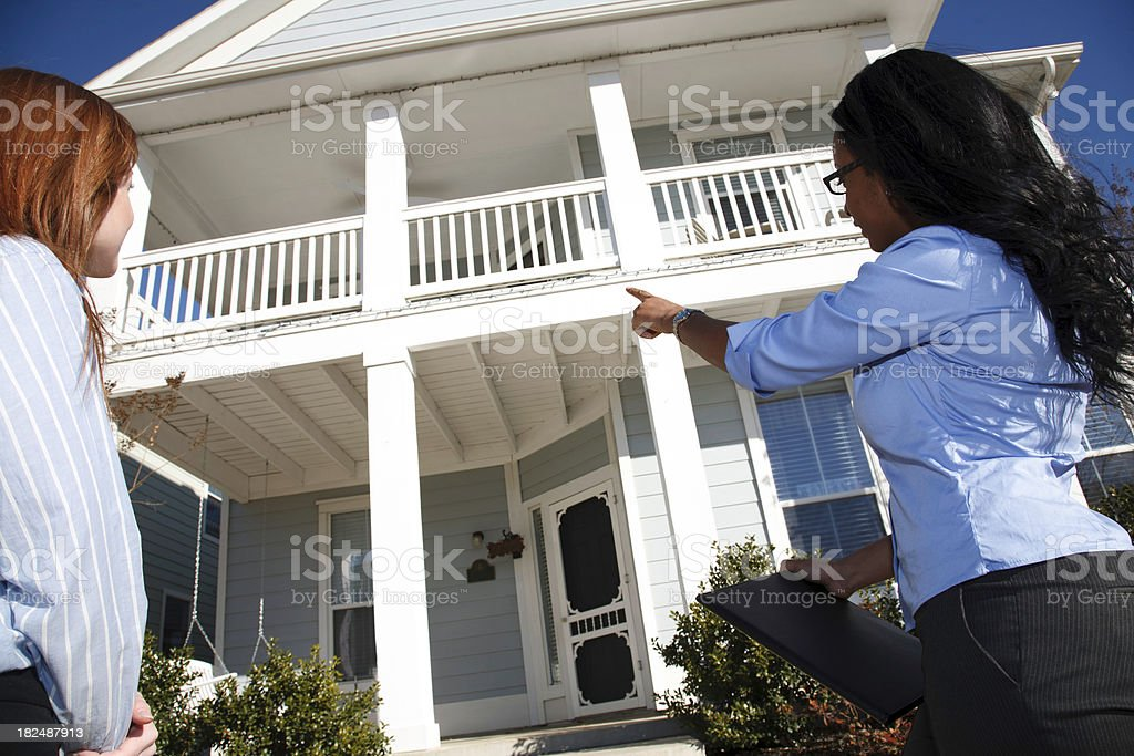 Realtor Pointing at Features of Home For Sale to Buyer royalty-free stock photo
