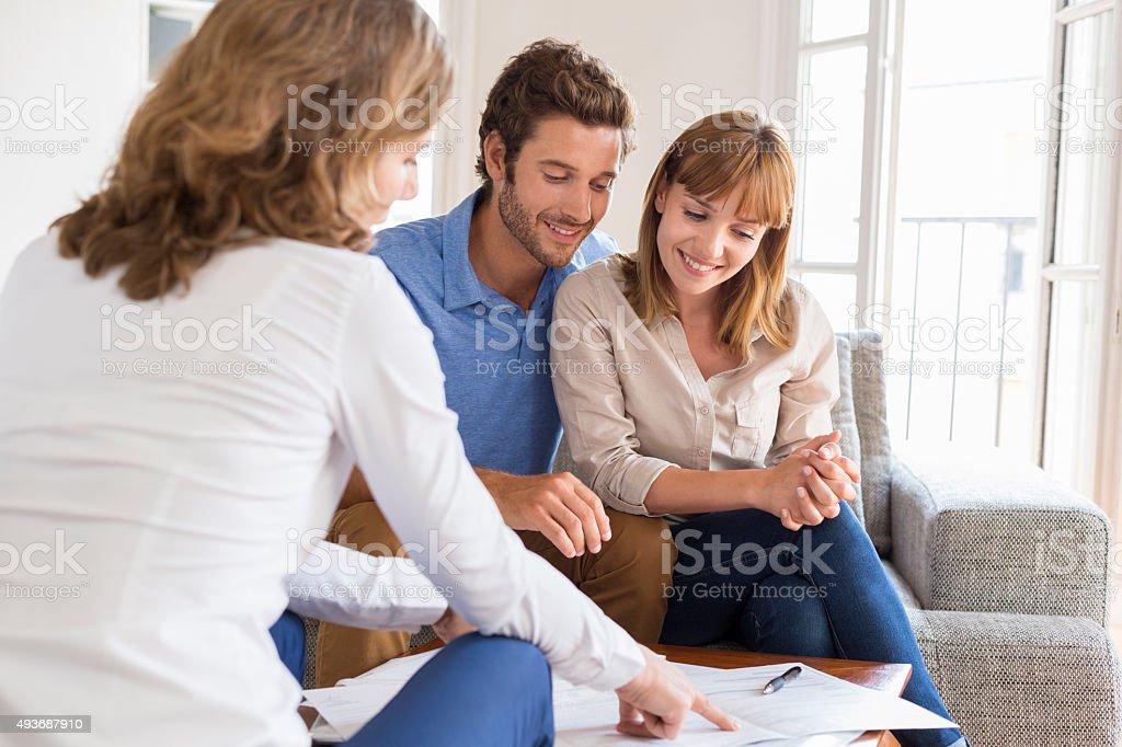 Immobilienmakler präsentiert ein Vertrag für house Investitionen für ein Paar – Foto