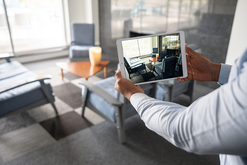 Realtor showing a property through an online video call using a tablet computer - real estate concepts