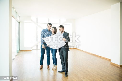istock Realtor Showing Architectural Plan To Couple In New House 1023541622
