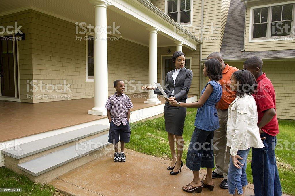 Agence immobilière montrant famille autour de la maison en vente photo libre de droits