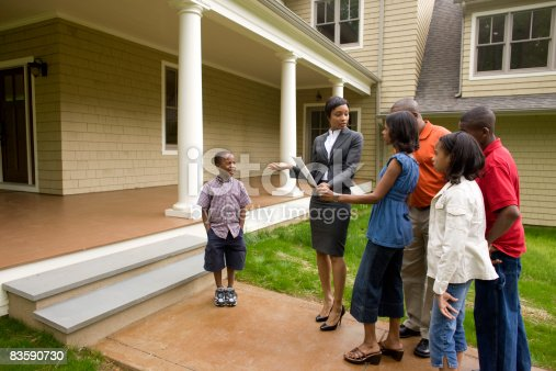 istock Realtor showing family around house for sale 83590730