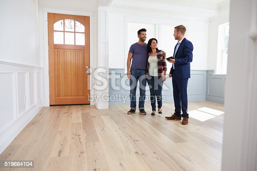 istock Realtor Showing Hispanic Couple Around New Home 519664104