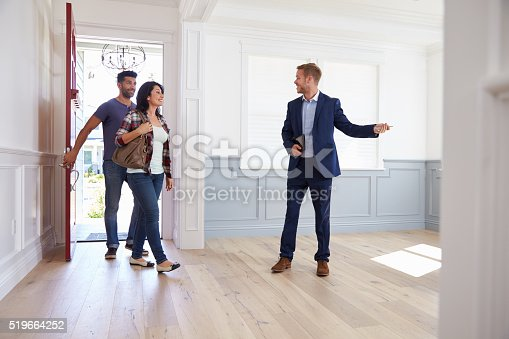 istock Realtor Showing Hispanic Couple Around New Home 519664252