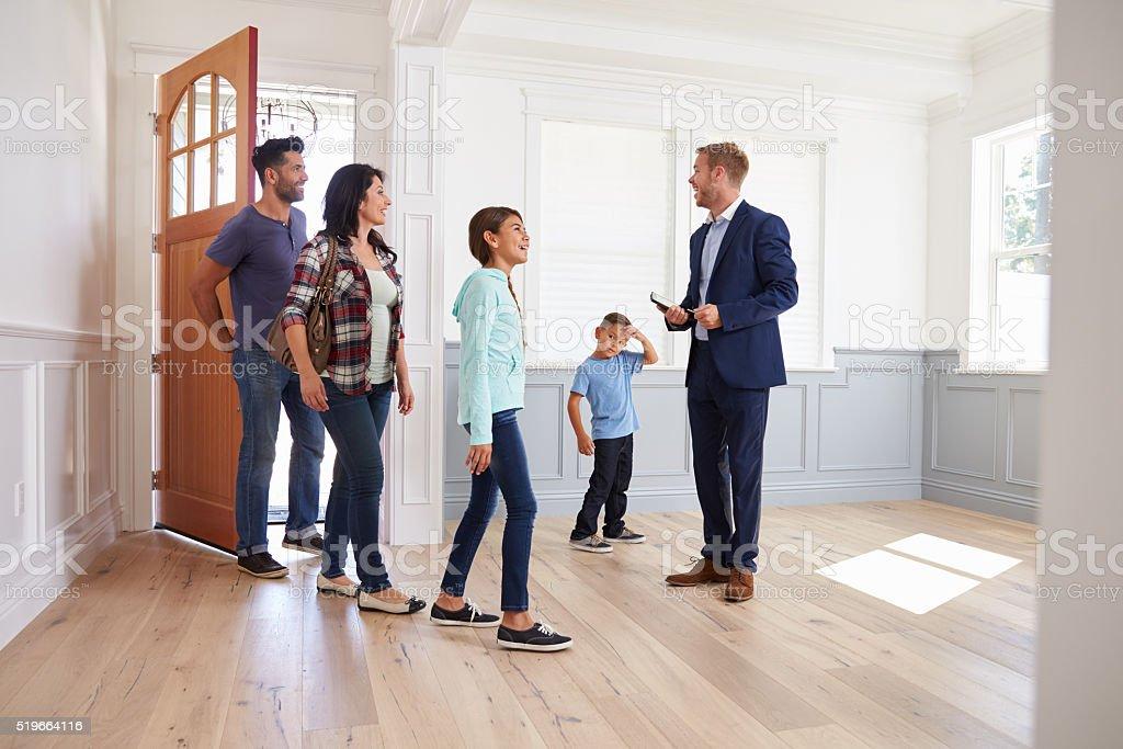 Realtor Showing Hispanic Family Around New Home stock photo