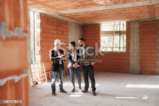 istock Realtor Showing New Home To Happy Married Couple 1087578414