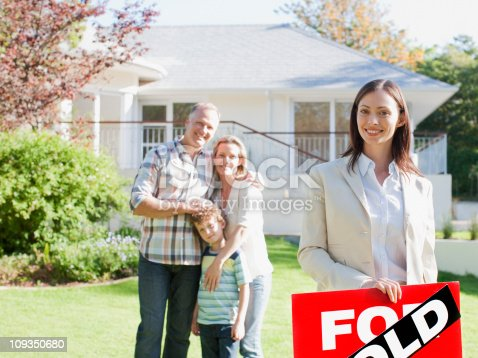 istock Realtor standing with family in front of new house 109350680