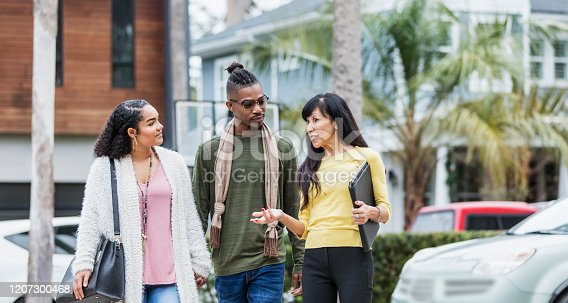 istock Realtor walking with young African-American couple 1207300468