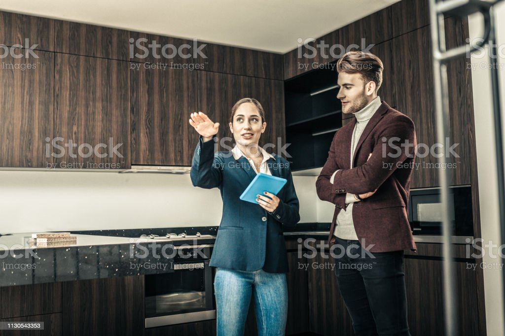 Realtor wearing blue jacket telling the advantages of house stock photo