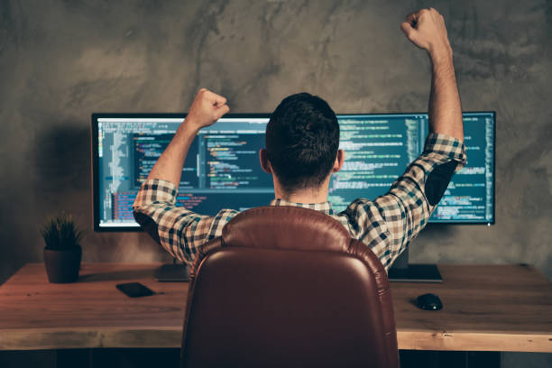 Rear back behind view of brunet guy wearing checked shirt professional expert sitting in front of screen celebrating accomplishment at wooden industrial interior work place station Rear back behind view of brunet guy wearing checked shirt professional expert, sitting in front of screen celebrating accomplishment at wooden industrial interior work place station nerd stock pictures, royalty-free photos & images