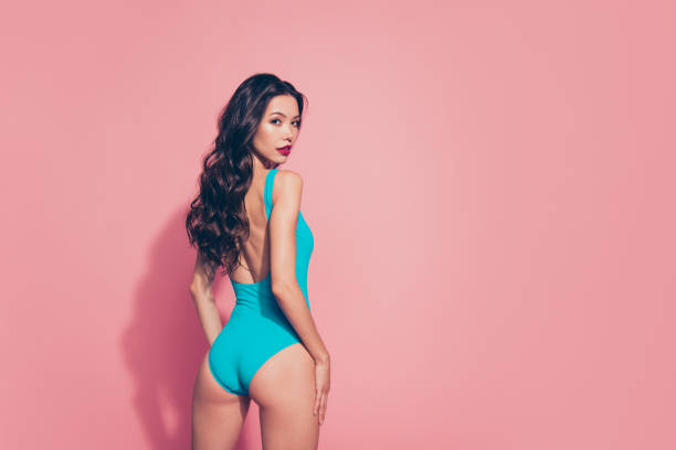 Rear back half-turned view portrait of nice sweet tender lovely Rear back half-turned view portrait of nice sweet tender lovely luxury attractive adorable charming wavy-haired lady shiny bright vivid look red lips isolated over pink background hot sexy butts stock pictures, royalty-free photos & images