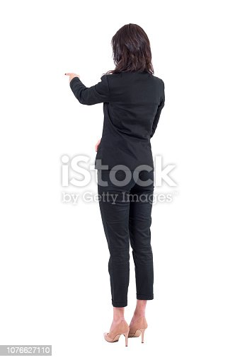 istock Rear back view of business woman in suit interacting with touch screen or pointing finger at presentation 1076627110