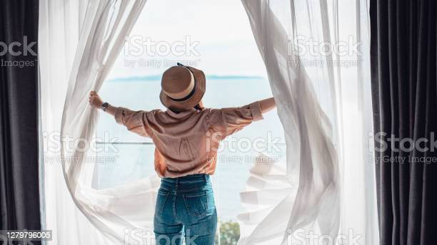Photo of Rear back view woman opening white curtains enjoy sea view, Happy  traveller stay in high quality hotel.