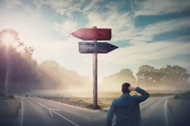 achterste zakenman voor crossroad en wegwijzer pijlen toont twee verschillende cursussen, linker-en rechter richting te kiezen. weg splitst in verschillende richtings richtingen. moeilijke beslissing, keuze concept. - dwarsweg stockfoto's en -beelden