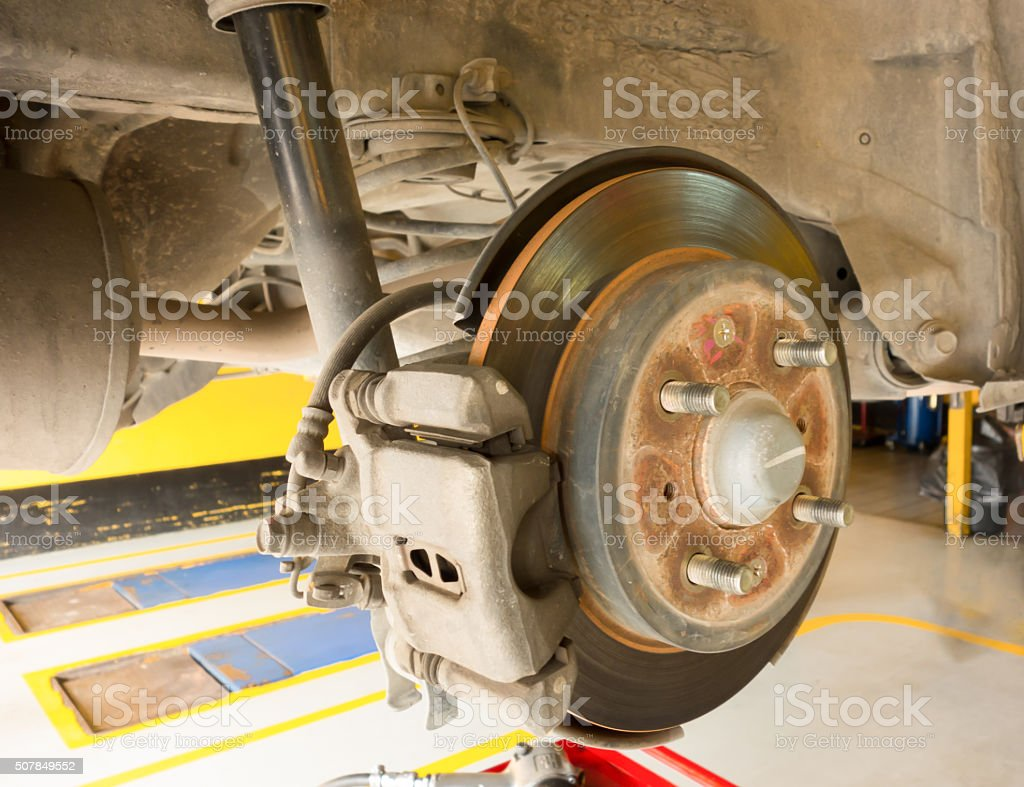 Rear disc brake car in process of new tire replacement stock photo