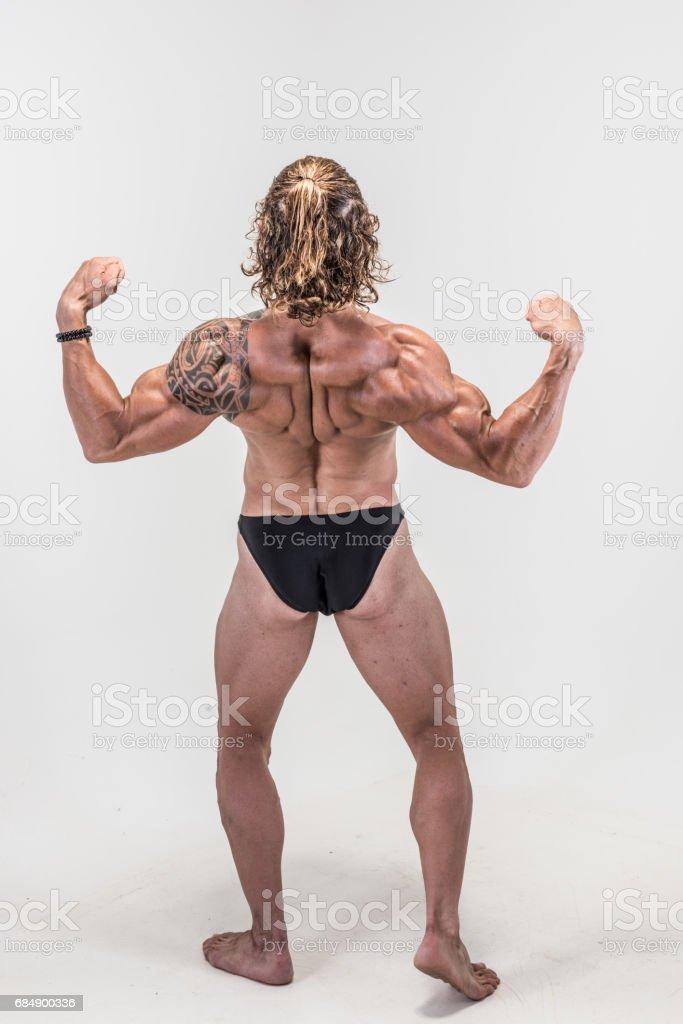 Rear double biceps pose from muscular athlete Lizenzfreies stock-foto