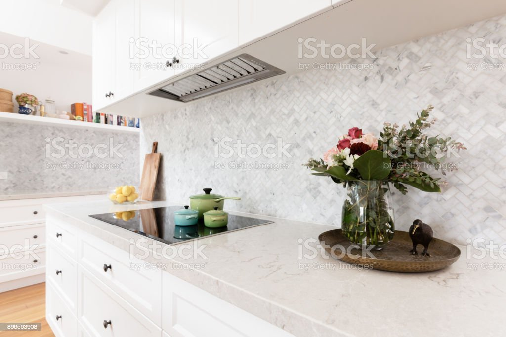Rear kitchen bench styled with cut flowers and colorful saucepans – zdjęcie