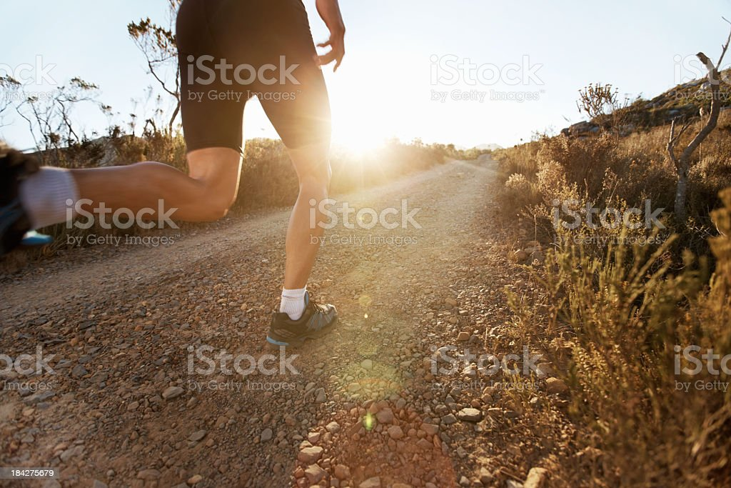 Rear leg view of a man jogging the rocky countryside royalty-free stock photo