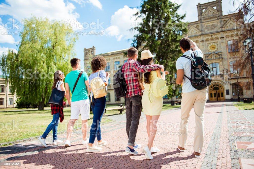 6 명의 다민족 학생의 뒤쪽 낮은 각도 보기입니다. 그들은 대학 건물을 걷고 있다 고 몸짓, 아이디어 공유, 본딩 프로젝트 토론 스톡 사진