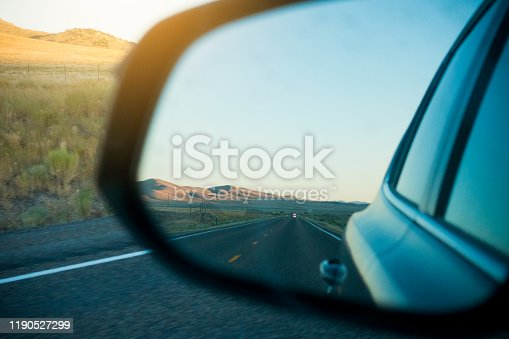 Rear Mirror of a Car on Highway During Sunset.