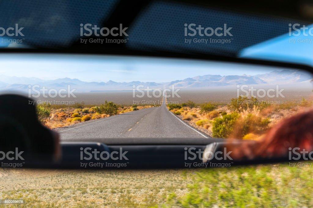 Rear mirror view on desert landscape in Nevada