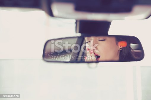 istock Rear mirror view reflection sleepy yawning woman driving her car after long hour drive. 836004576