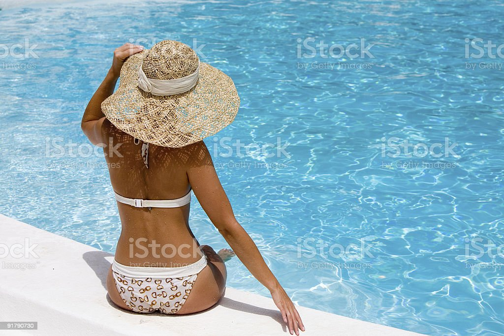 Rear of a woman with a hat relaxing beside a swimming pool royalty-free stock photo