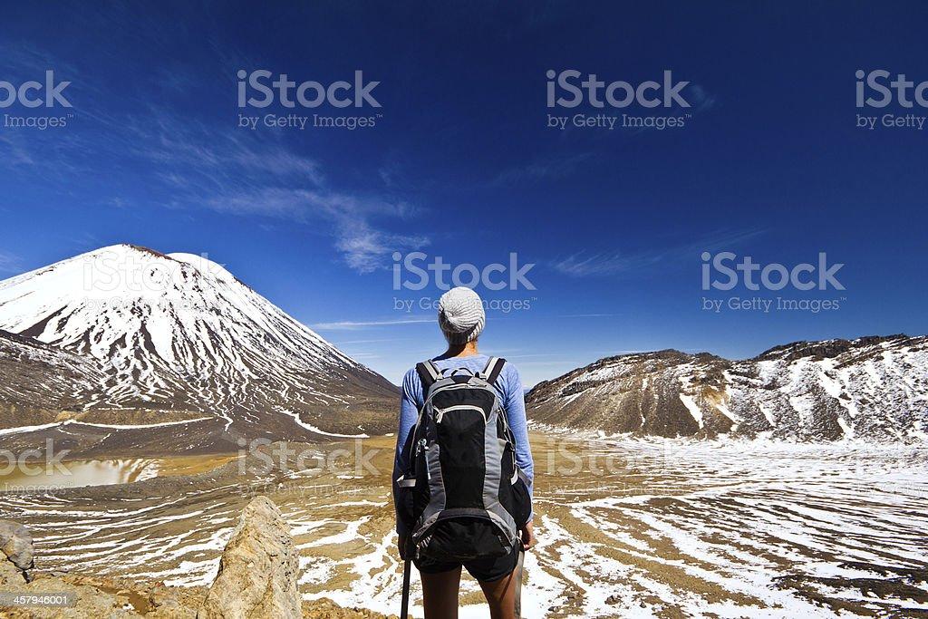 Rear of hiker facing mountains stock photo