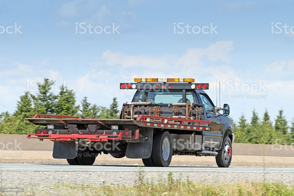 Rear Quarter View Of Flatbed Tow Truck On Highway stock photo