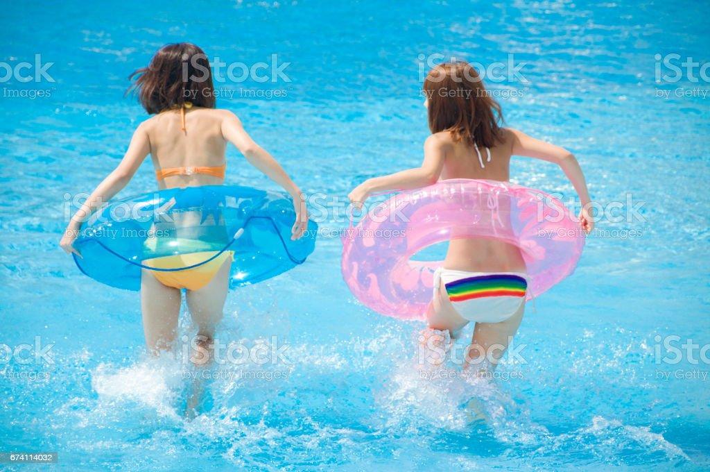 後方查看 2 婦女浮泳裝在游泳池裡玩 免版稅 stock photo
