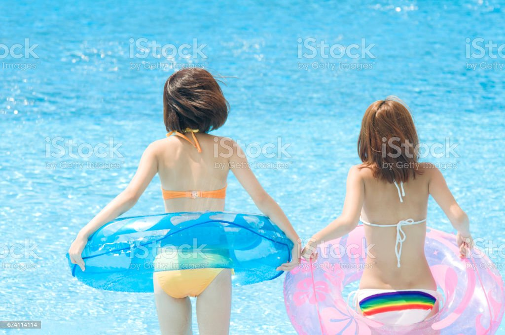 Rear view 2 women playing in the pool with float swimsuit royalty-free stock photo