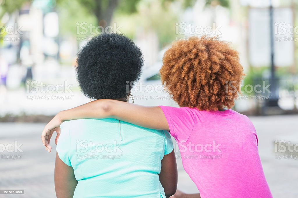 Rear view, adult daughter with arm around mother stock photo