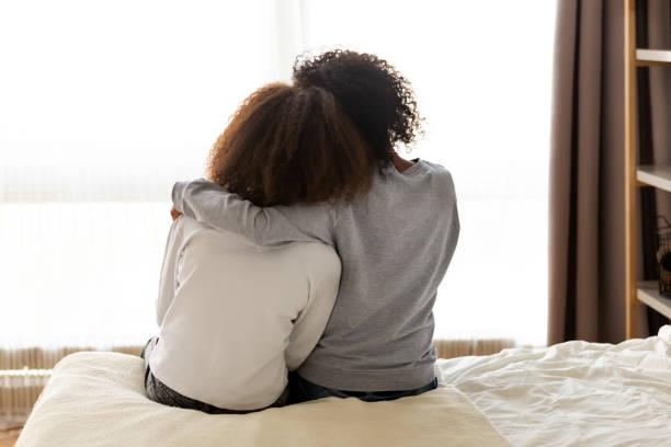 vista trasera madre africana e hija abrazando sentado en la cama - hija fotografías e imágenes de stock