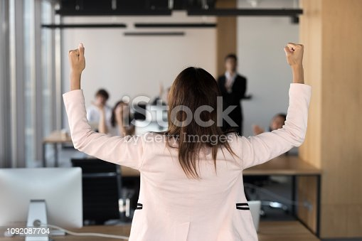 istock Rear view african team leader raising hands celebrating victory 1092087704