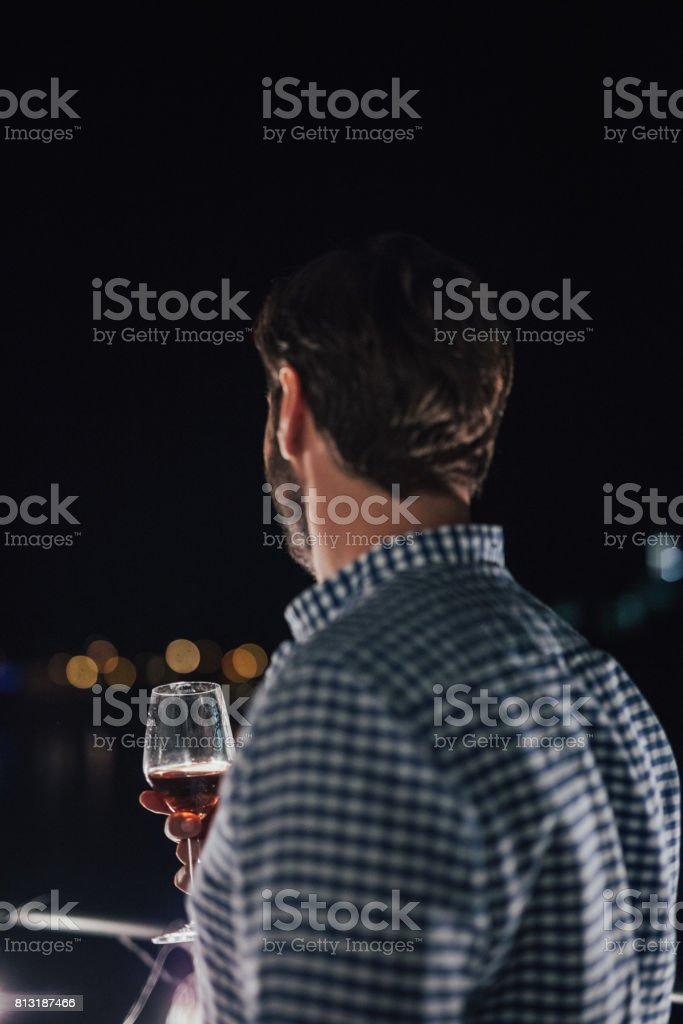 Handsome man wearing plaid shirt on the terrace is drinking alcohol....