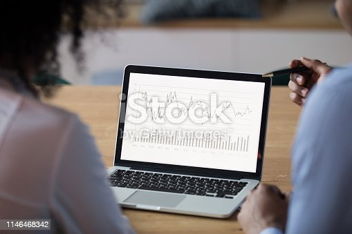 istock Rear view at african analysts analyze financial report on laptop 1146468342
