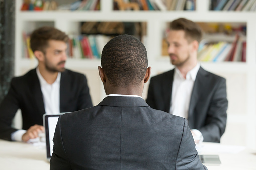 istock Rear view at african businessman sitting against two caucasian men 912234948