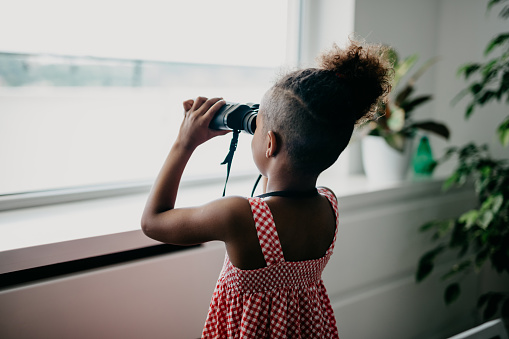 Rear view at african kid looking through binoculars