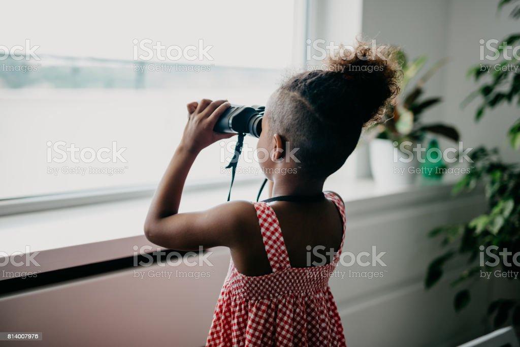 Rear view at african kid looking through binoculars stock photo