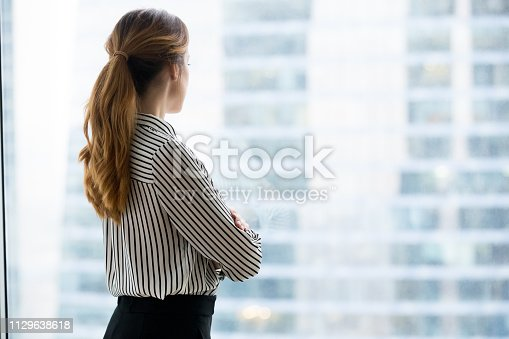 Rear back view at confident rich businesswoman looking forward through glass window of skyscraper building dreaming of success thinking of future business vision and new goals enjoying city view