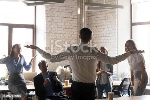 509032417 istock photo Rear view at leader raising hands celebrating success with team 1085713956
