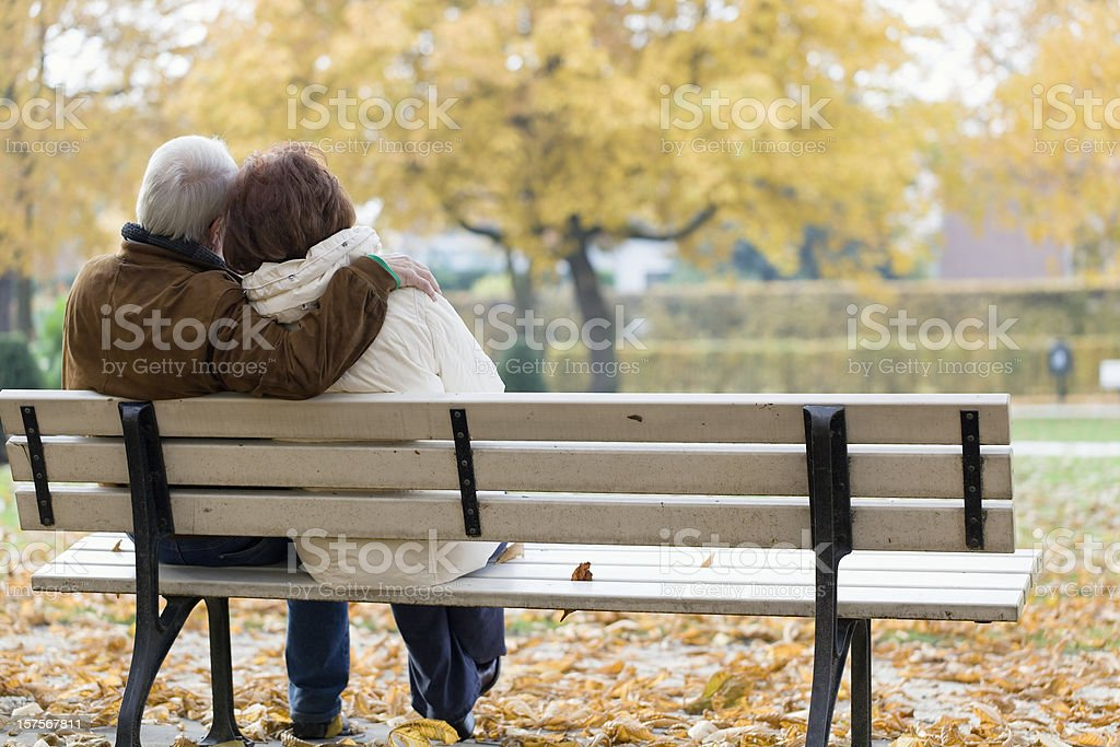 Rear view at senior couple on park bench in autumn royalty-free stock photo