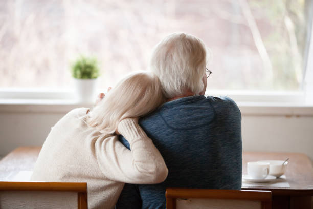 rear view at senior grey haired couple relaxing at home - casa reforma imagens e fotografias de stock