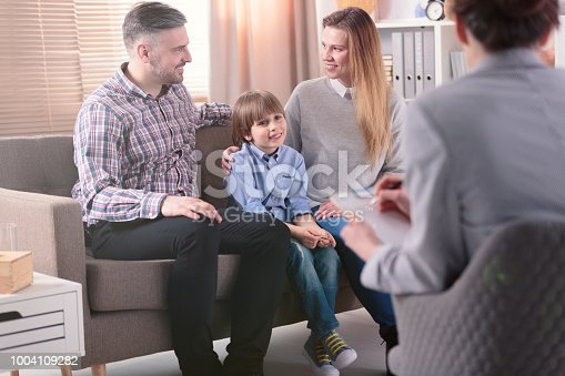 istock Rear view at successful female psychotherapist helping young family with a child to solve problems in relationship. Happy family in the background 1004109282