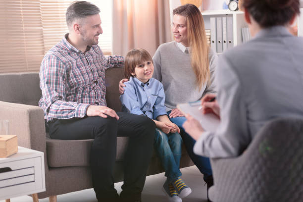 Rear view at successful female psychotherapist helping young family with a child to solve problems in relationship. Happy family in the background stock photo