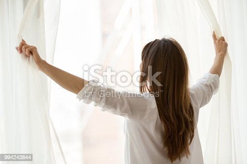 Rear view at woman opening window curtains at home or hotel starting new day, enjoying wellbeing or light good pleasant morning looking out feeling happy, breathing fresh air, relaxing on weekend